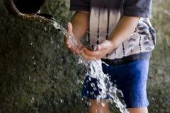 Enfant à la fontaine de tuyau d'eau potable  Images stock