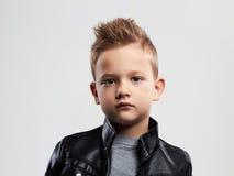 Enfant à la mode dans le manteau en cuir enfant élégant avec la coupe de cheveux à la mode images stock