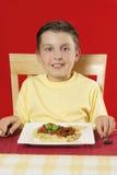 Enfant à la table avec la plaque de la nourriture images stock