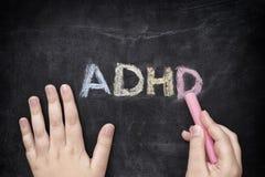 Enfant écrivant ADHD sur le tableau noir images stock