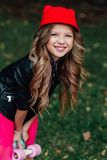 Enfant élégant de petite fille de mode de portrait posant avec la planche à roulettes sur le parc de ville images libres de droits