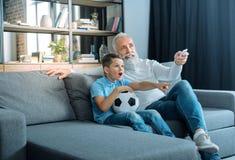 Enfant émotif regardant la TV avec le grand-père Photos libres de droits