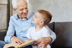 Enfant énergique mignon appréciant le temps avec le grand-papa image libre de droits