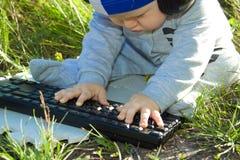 Enfant étudiant le clavier dehors Image libre de droits
