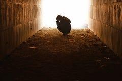 Enfant abandonné s'asseyant dans le tunnel dans la peine Images stock