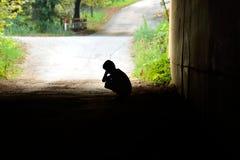 Enfant abandonné s'asseyant dans le tunnel dans la peine Photographie stock