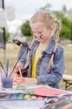 Enfant actif jouant dehors et peignant Photos libres de droits