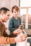 Enfant adorable désireux excité pour aider son papa avec les travaux domestiques photographie stock