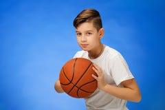Enfant adorable de garçon de 11 ans avec la boule de basket-ball Photographie stock