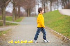 Enfant adorable, garçon, jouant en parc avec les canards en caoutchouc, ayant f Photographie stock