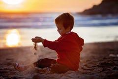 Enfant adorable, jouant sur la plage sur le coucher du soleil Images libres de droits