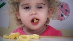Enfant adorable mangeant des bâtons de cercle de maïs banque de vidéos