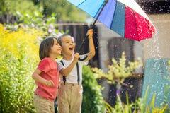 Enfant adorable mignon, garçon, jouant avec le parapluie coloré sous s images stock