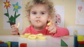 Enfant affamé mangeant des chips de maïs de maïs se reposant près de la table dans sa chambre clips vidéos