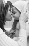 Enfant affectueux de fixation de mère dans des ses mains après 'bat' Images stock