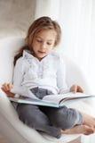 Enfant affichant un livre Photos libres de droits