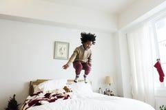 Enfant africain ayant un temps d'amusement sautant sur un lit image stock