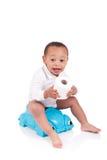 Enfant africain sur le jeu de pot avec du papier hygiénique, au-dessus du whi Image libre de droits