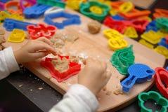 Enfant aidant à préparer des biscuits image libre de droits