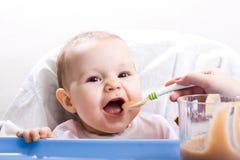 Enfant alimentant Photographie stock libre de droits