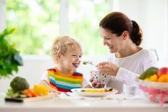Enfant alimentant de mère La maman alimente des légumes d'enfant image stock