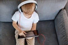 Enfant allègrement focalisé à l'aide de son comprimé photographie stock