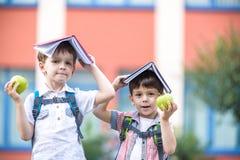 Enfant allant à l'école Garçon et son ami tenant des livres sur la tête Image stock