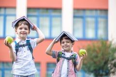 Enfant allant à l'école Le garçon et son ami tenant des livres sur la tête aiment le toit de maison le premier jour d'école Photo stock