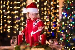 Enfant allumant une bougie au dîner de Noël Images stock