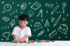 Enfant asiatique apprenant par le jeu avec son imagination au sujet des activités d'objet d'école d'approvisionnements de papeter photo stock