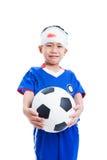 Enfant asiatique avec le traumatisme de la tête tenant un football et un cri Image libre de droits