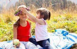 Enfant asiatique avec son amie caucasienne sur un pique-nique dans les montagnes La fille utilise un bandeau des fleurs sur la tê Photographie stock