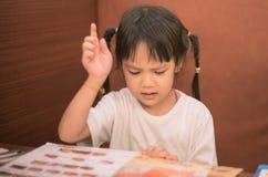 Enfant asiatique ayant la difficulté choisissant le menu photo libre de droits