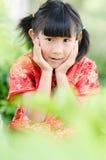 Enfant asiatique dans le cheongsam de chinois traditionnel avec le backgro de nature images libres de droits