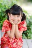 Enfant asiatique dans le cheongsam de chinois traditionnel avec le backgro de nature photo stock