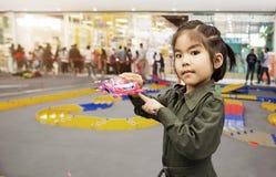 Enfant asiatique de fille avec le jouet de voiture d'exposition de suite de service Images libres de droits