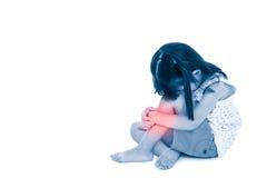 Enfant asiatique de tristesse s'asseyant avec l'espace de copie Fille blessée au tibia, photo stock