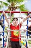 Enfant asiatique heureux jouant sur le terrain de jeu Images stock
