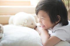 Enfant asiatique jouant avec le chiot de chien de traîneau sibérien Photos stock