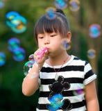 Enfant asiatique jouant les bulles de soufflement Photo stock
