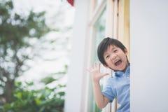 Enfant asiatique mignon à la fenêtre ouverte photos libres de droits