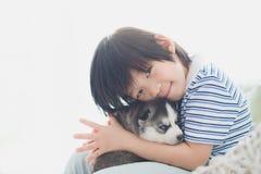 Enfant asiatique mignon jouant avec le chiot de chien de traîneau sibérien Images stock