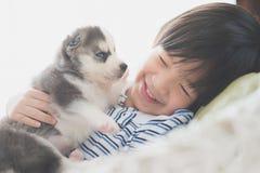Enfant asiatique mignon jouant avec le chiot de chien de traîneau sibérien Photographie stock