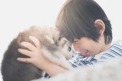 Enfant asiatique mignon jouant avec le chiot de chien de traîneau sibérien Images libres de droits