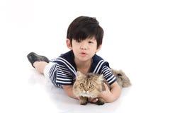 Enfant asiatique mignon se trouvant avec le chat tigré Photographie stock