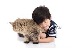 Enfant asiatique mignon se trouvant avec le chat tigré Image stock