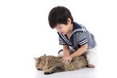 Enfant asiatique mignon se trouvant avec le chat tigré Photos stock