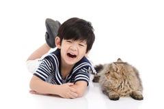 Enfant asiatique mignon se trouvant avec le chat tigré Photo libre de droits