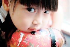 Enfant asiatique observant sur le cheval de jouet Photographie stock