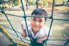 Enfant asiatique s'élevant dans une corde au terrain de jeu d'enfants Vintage t Photographie stock